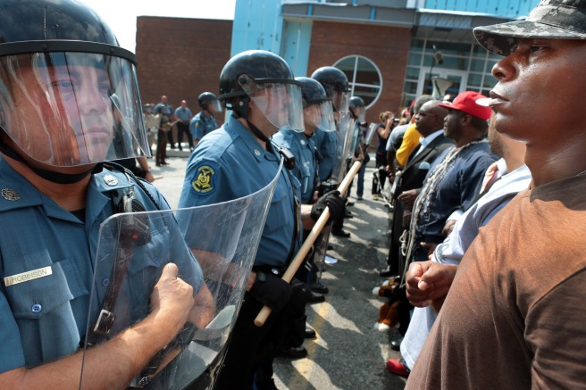 Protestor Boss Bastain of St. Louis locks arms with others as they confront Missouri State Highway Patrol troopers in front of the Ferguson police station on Monday, Aug. 11, 2014.  Marchers are entering a third day of protests against Sunday's police shooting of Michael Brown. (AP Photo/St. Louis Post-Dispatch, Robert Cohen)